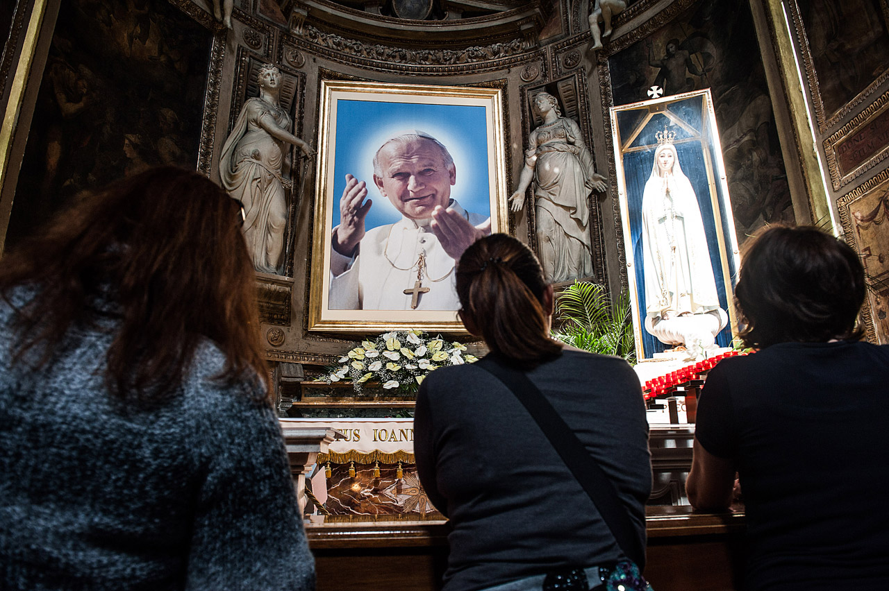 People kneel in front of a painting depincting John Paul II, Roma, Italy ©Alessia GIULIANI/CPP
